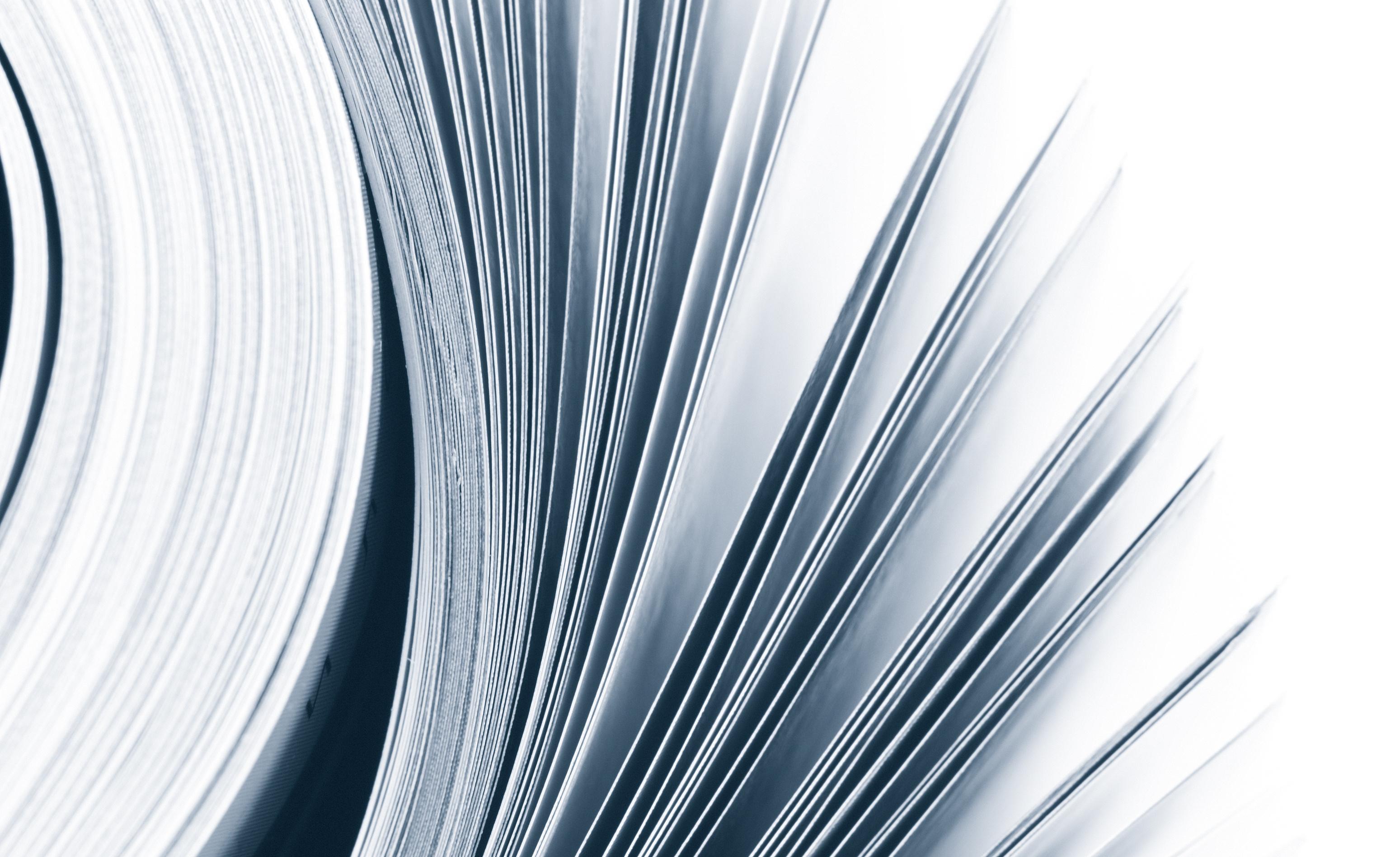 Close-up of magazine pages on white background. Toned monochrome image. Shallow DOF, focus on edges.
